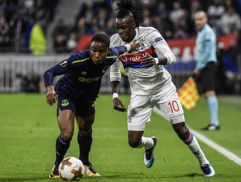 Everton's Ademola Lookman, left, tries to get away from Lyon's Bertrand Traore.