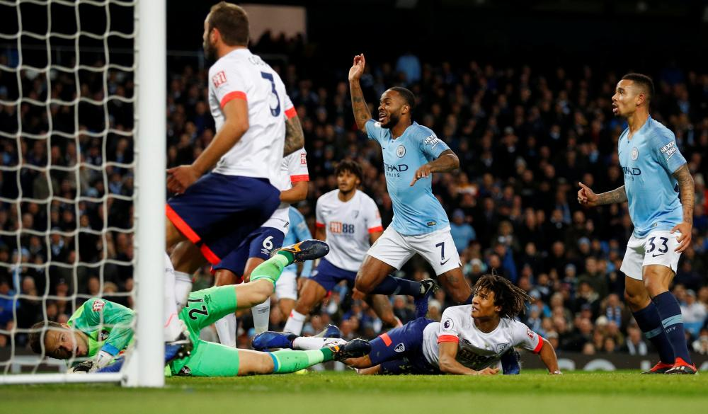 Manchester City's Raheem Sterling scores from close range.