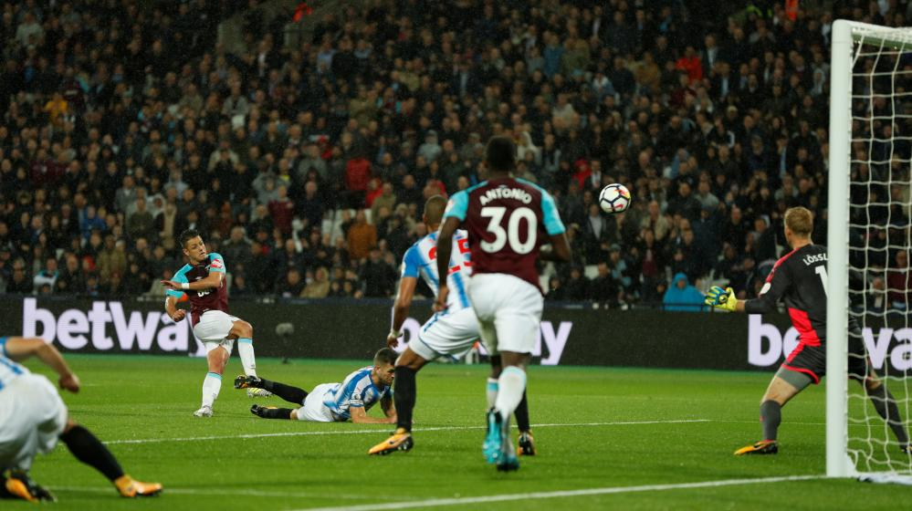 Javier Hernandez leans back and his shot hits the bar.