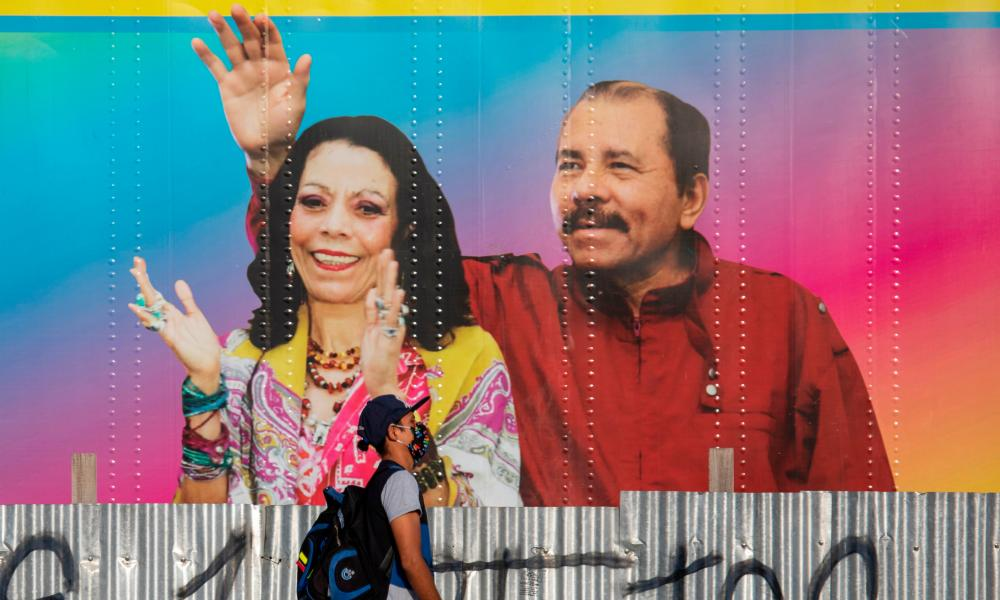 A man walks by a mobile health clinic displaying a picture of Nicaragua's President Daniel Ortega and his wife Vice-President Rosario Murillo in Managua on 14 April 2020.
