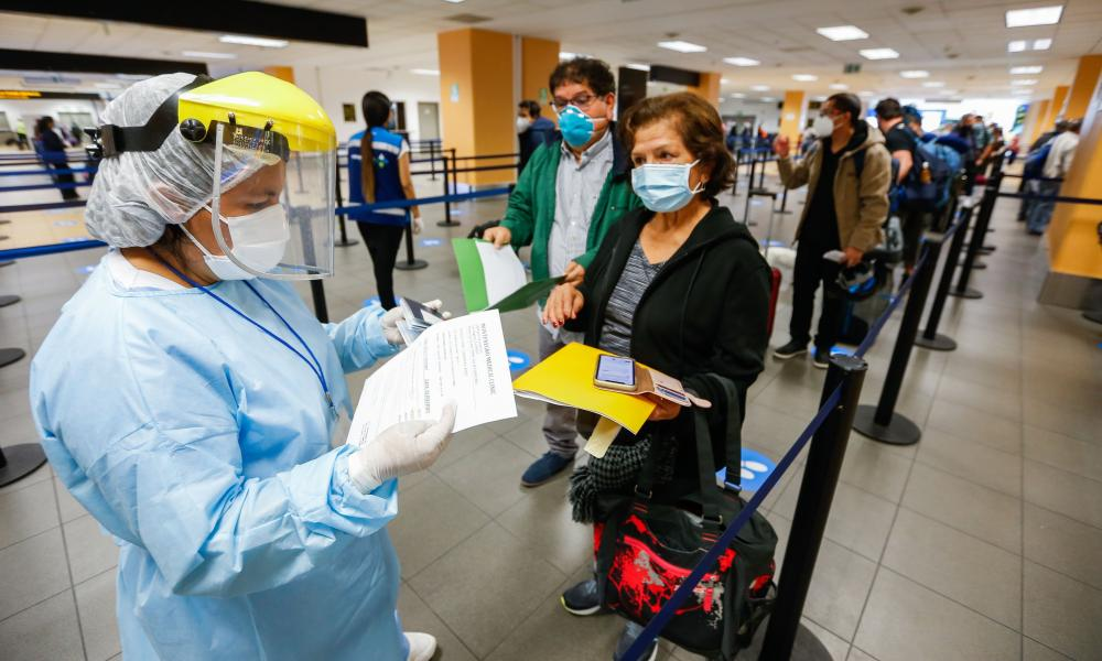 A health worker in personal protective clothing checks documents of masked airport travellers in Peru's Jorge Chavez airport.