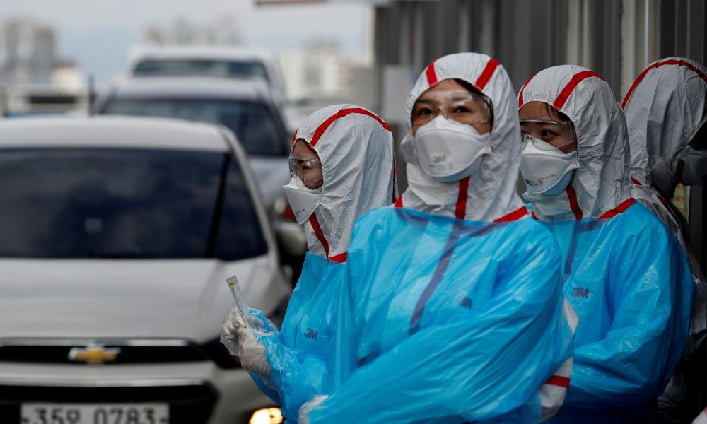 Medical staff in protective gear work at a 'drive-thru' coronavirus testing centre in Yeungnam University Medical Centre in Daegu, South Korea, 3 March 2020.