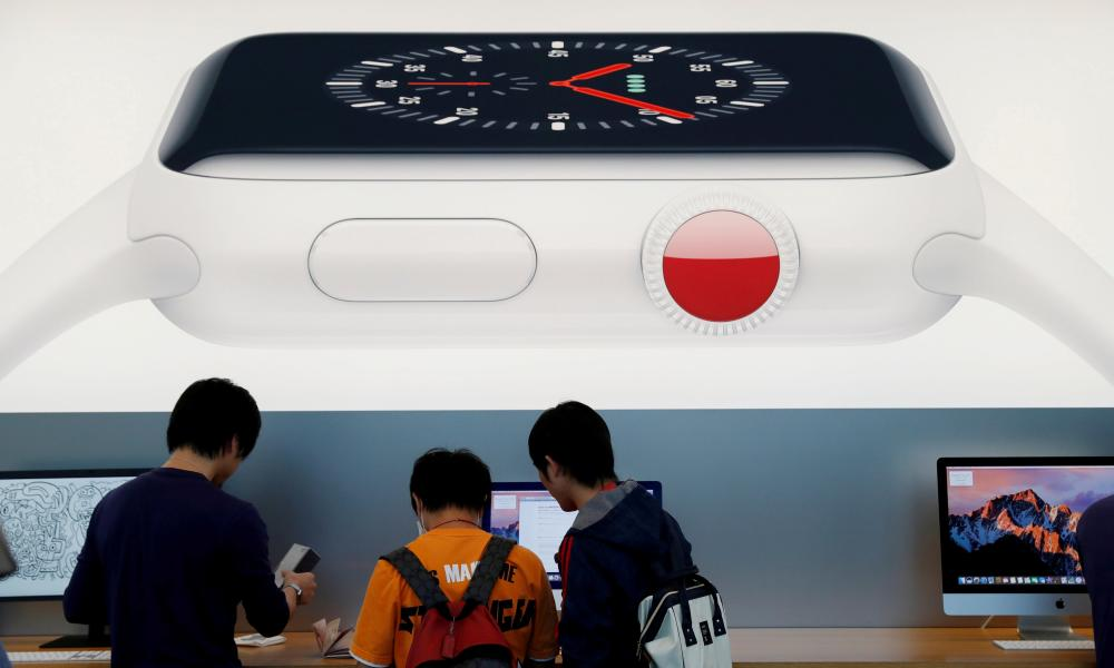 Customers are seen under a picture of new Apple Watch Series 3 after it goes on sale at the Apple Store in Tokyo's Omotesando shopping district, An tSeapáin, Meán Fómhair 2017.