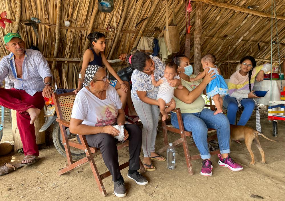 Yirley Velazco, seated with baby, visits families in a rural area of Montes de Maria