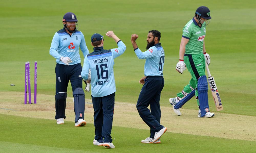 Ireland's batsman Kevin O'Brien (right) walks back to the pavilion after getting bowled out by England's Adil Rashid (second right) .