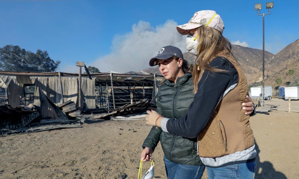 Virginia Padilla, left, who lost 29 horses at her Padilla Ranch on Little Tujunga Road is comforted by a horse trainer Shelby Hope.