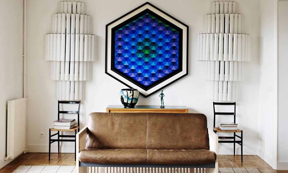 A painting of luminous blues with a pair of 1960s tubular glass sconces from Milan Centrale railway station either side of it.