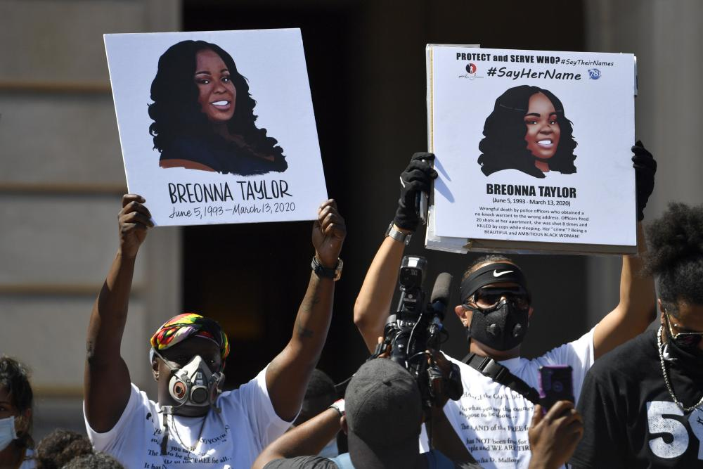 Signs are held up showing Breonna Taylor during a rally on the steps of the Kentucky State Capitol in Frankfort.