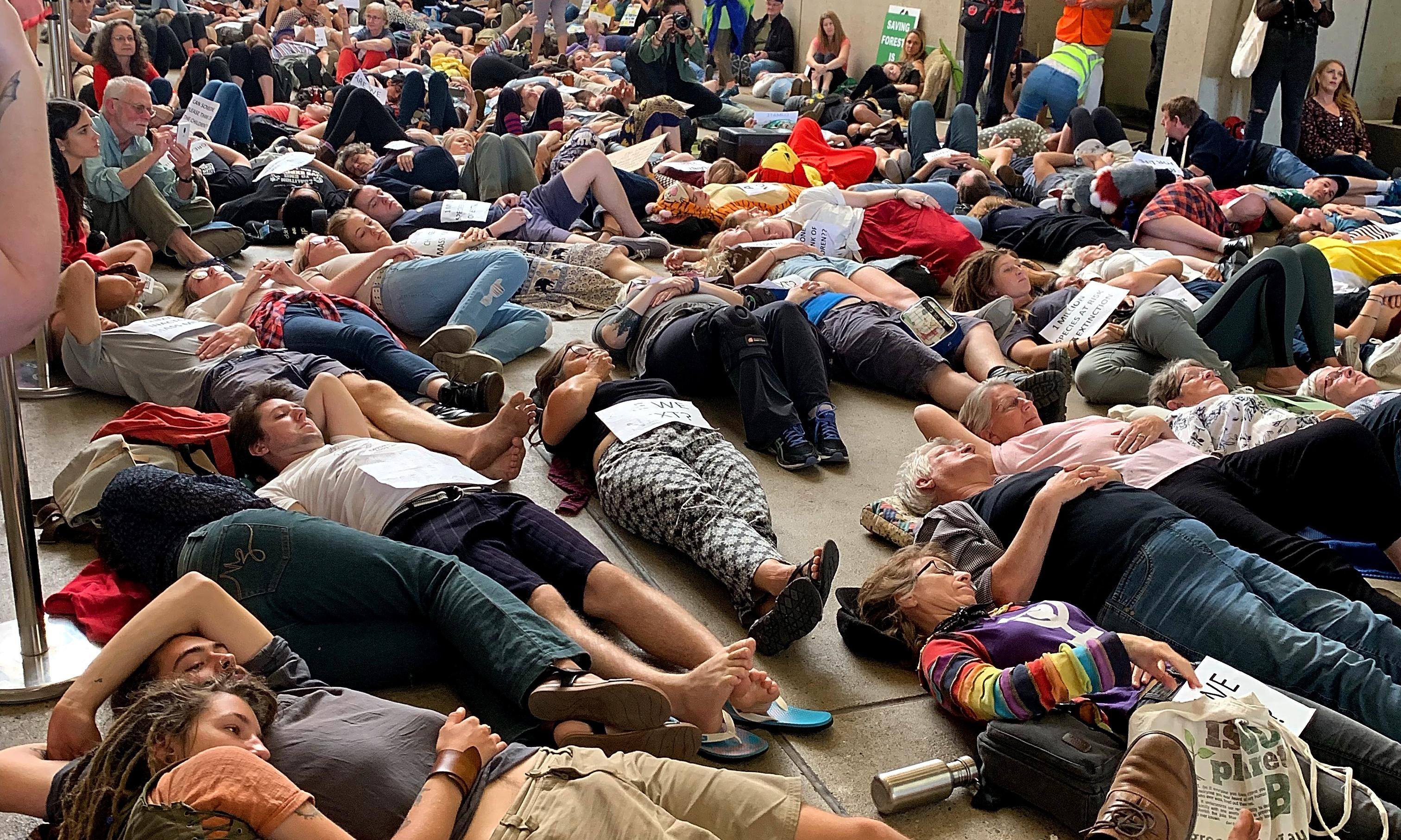 Climate protesters stage 'die-in' at Queensland Museum's dinosaur exhibit