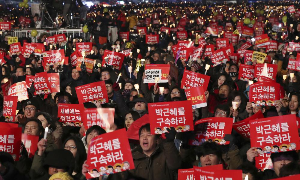 Protesters demand the president's resignation in Seoul, South Korea. The signs read: 'Arrest Park Geun-hye'.