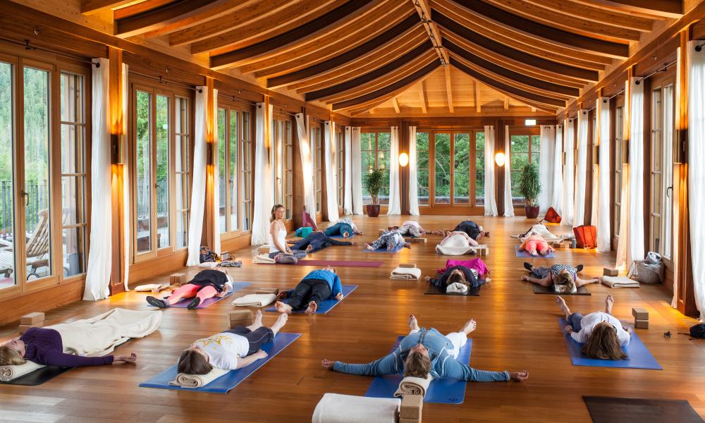 A yoga class in a wood and glass hut