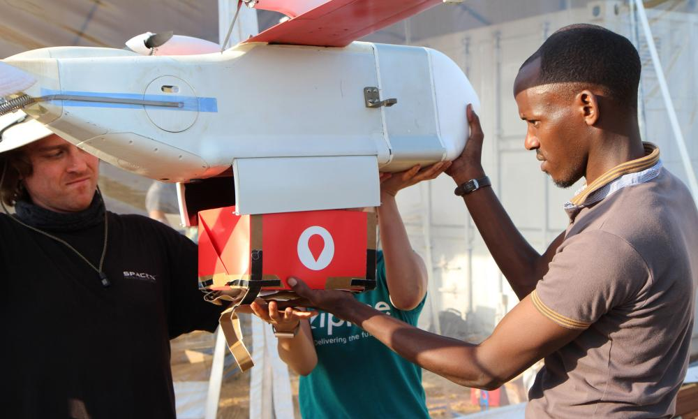 A technician from Zipline installs a cardboard box with a paper parachute in a drone in Muhanga