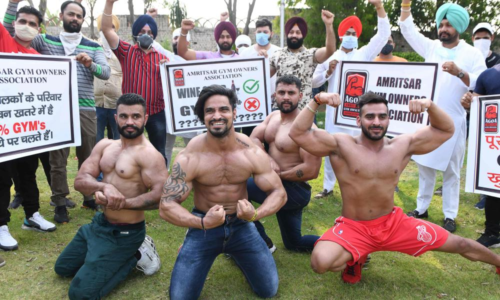 Gym owners and trainers hold banners as they stage a protest demanding the government to allow them to open their fitness centres, on the outskirts of Amritsar on June 7, 2020. (Photo by NARINDER NANU/AFP via Getty Images)