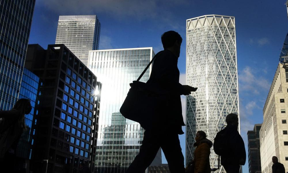 Office workers and commuters walk through Canary Wharf in London during the morning rush hour.