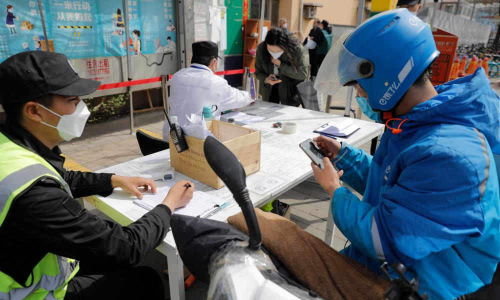 A food delivery man scans the code on a mobile phone to show the green code as he prepares to enter into 798 Art Zone in Beijing.