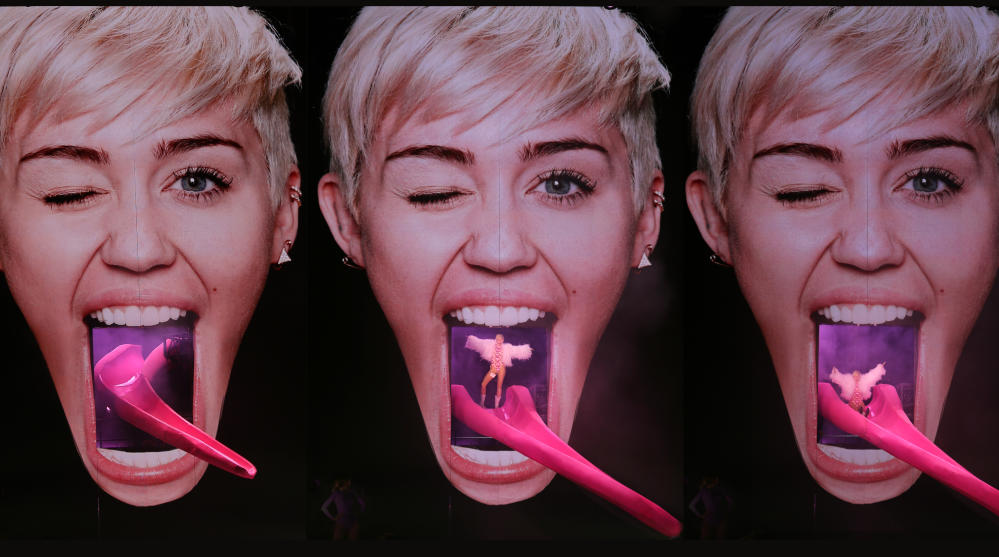 Miley Cyrus emerges from her own mouth, as designed by Devlin, on her 2014 tour.