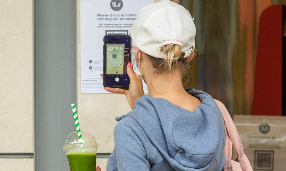 A woman checks in to a shop using a QR code