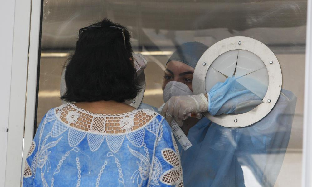 Medic takes a sample from a woman to test for Covid-19 at an apartment complex where dozens of cases have been registered among a community of Bulgarian farm workers.