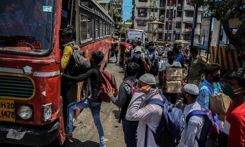 Migrant workers board a bus in Mumbai to go to their home towns.