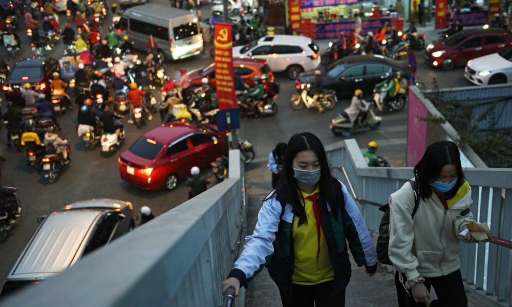 Gilrs walks in an overpass as they wear protective masks in the street in Hanoi, Vietnam