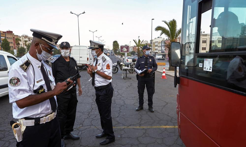 Moroccan police check to see if a bus meets the number of passengers allowed at a checkpoint in Casablanca, Morocco, Monday, Sept. 21, 2020.