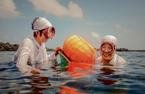 In South Korea, 45% of the diving women of Jeju are over the age of 70. Ja Kang Song, 71, and Ja Hyun Su, 72, dive for shellfish and are the main breadwinners for their families. Routinely diving to depths of 20m and staying under for an average of two to three minutes, the pressure on the body takes its toll and, like many others, burst eardrums have left Ja Hyun Su deaf. Each season, between seven and 10 women die diving the waters around Jeju Island