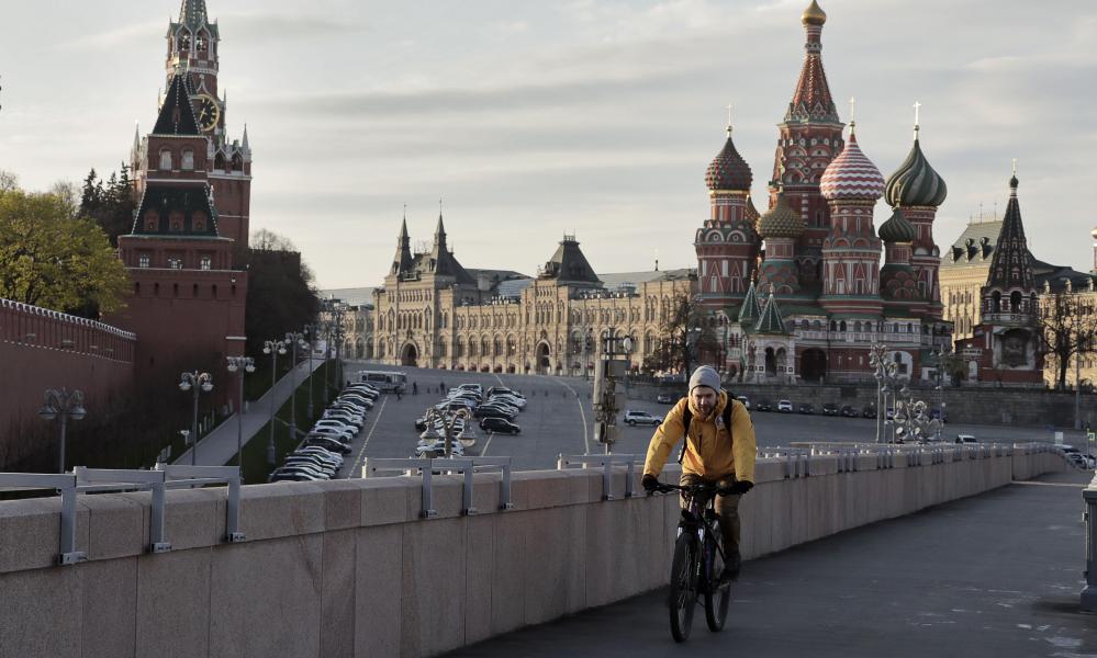 A man riding a bicycle along the Bolshoi Moskvoretsky Bridge in Moscow.
