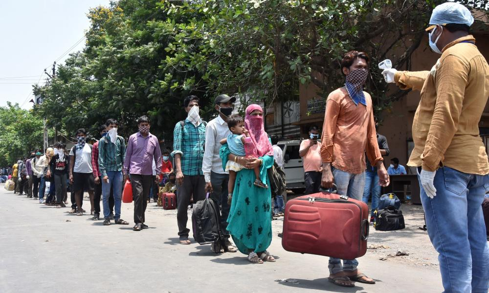 A health worker (R) checks the temperature of stranded migrant workers before they board on special busses to return to their hometowns during a government-imposed nationwide lockdown as a preventive measure against the COVID-19 coronavirus, near Surat, some 290 km south of Ahmedabad on May 1, 2020. (Photo by STR / AFP) (Photo by STR/AFP via Getty Images)
