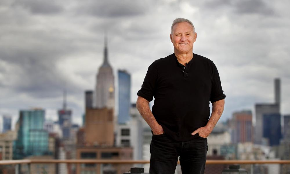 Ian Schrager standing, smiling, with the city behind him