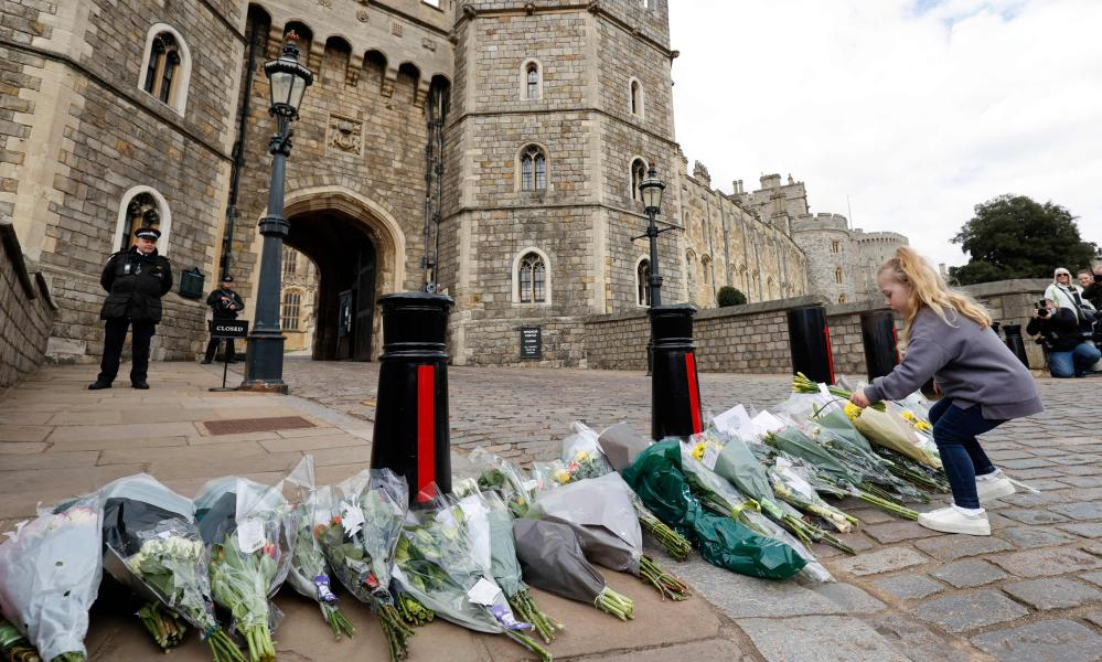 Children add to the floral tributes for Prince Philip outside the Henry VIII Gate of Windsor Castle.