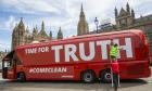 A Vote Leave campaign bus is rebranded outside the Houses of Parliament in Westminster by the environmental campaign group Greenpeace on 18 July 2016.