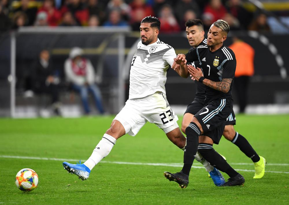 Emre Can shoots under pressure from Roberto Pereyra of Argentina.