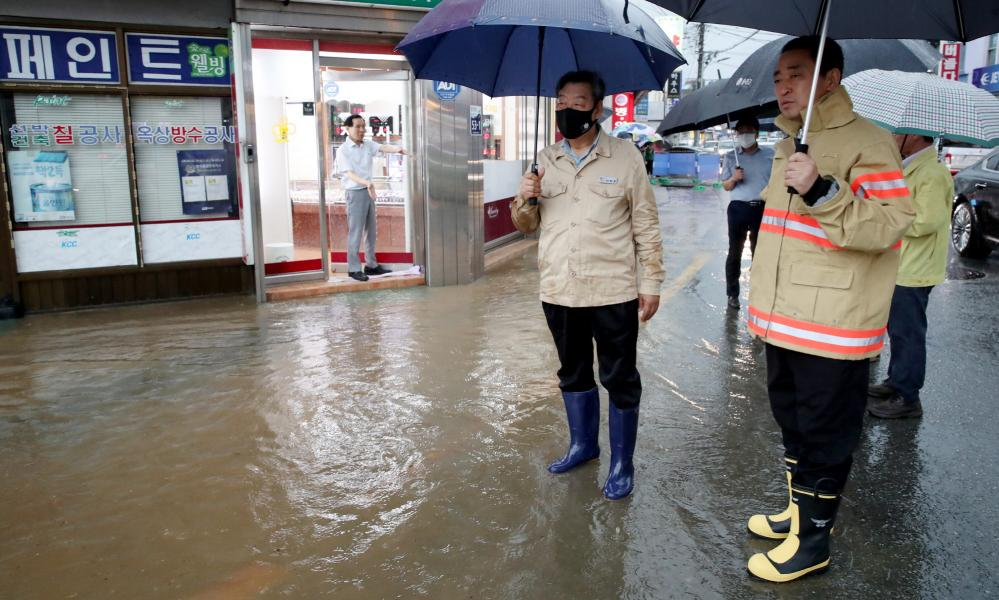 People carry umbrellas while wearing rubber galoshes as they wade on a flooded street in Taean, South Korea, 23 July 2020.