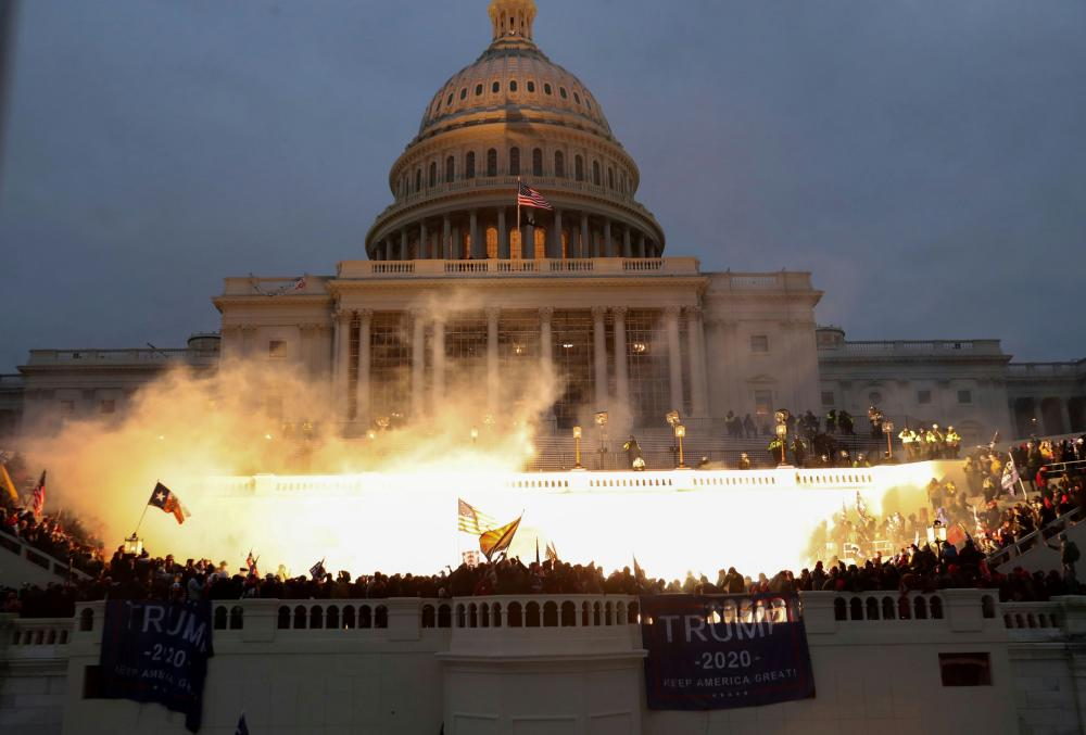 An explosion caused by a police munition is seen while supporters of Donald Trump gather in front of the US Capitol building.