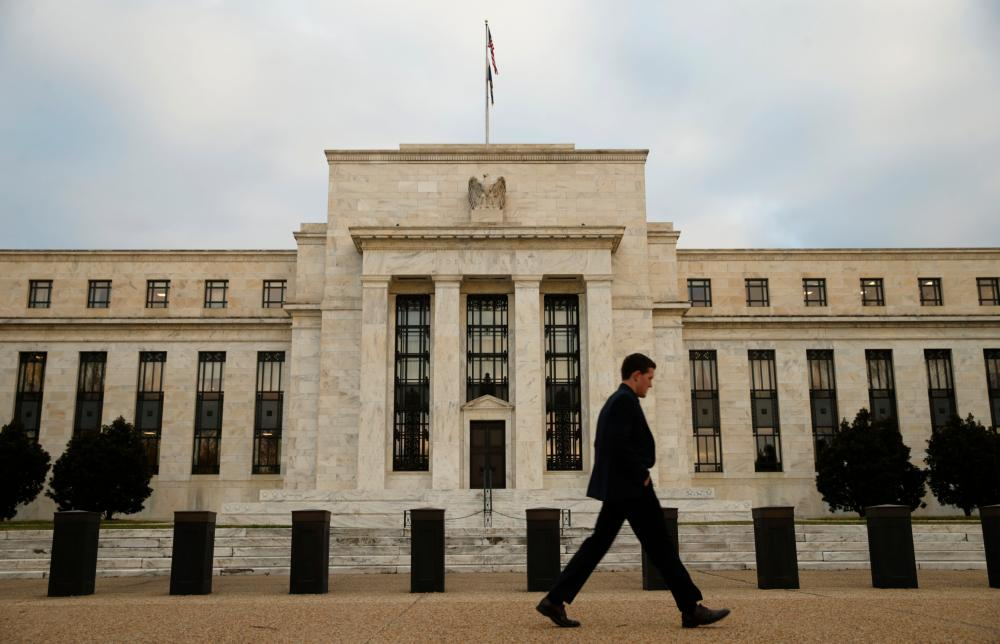 A man walks past the Federal Reserve in Washington, December 16, 2015. The U.S. central bank is widely expected on Wednesday to hike its key federal funds rate by a modest 0.25 percent. It would be the first tightening in more than nine years and a big step on the tricky path of returning monetary policy to a more normal footing after aggressive bond-buying and near-zero borrowing costs. REUTERS/Kevin Lamarque