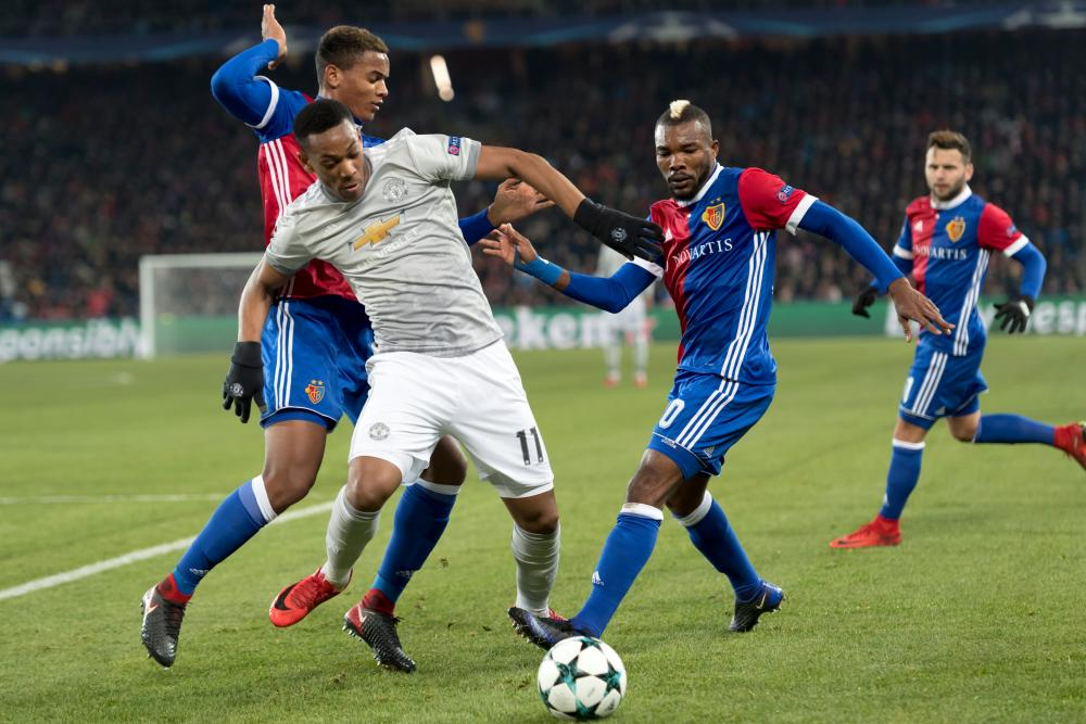 Manchester United's Anthony Martial and Basel's Geoffroy Serey Die during the UEFA Champions League game.