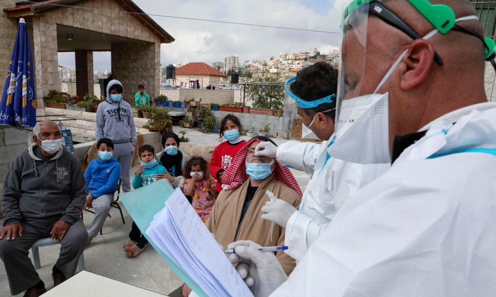 Doctors affiliated with the Palestinian ministry of health and working in a mobile clinic, perform checkups on 15 members of the al-Awawdeh family infected with Covid-19 and administer treatments, at their home in Dura village southwest of Hebron city in the occupied West Bank, on 3 March, 2021.