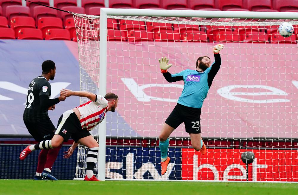 Exeter City goalkeeper Jonathan Maxted makes a save from Vadaine Oliver's header.