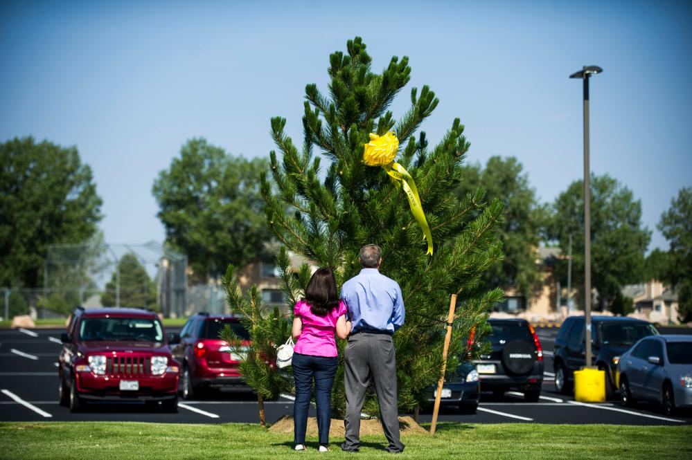 Caren Teves and Tom Teves stand in front of a tree with a ribbon bearing the name of their late son, Alex Teves.