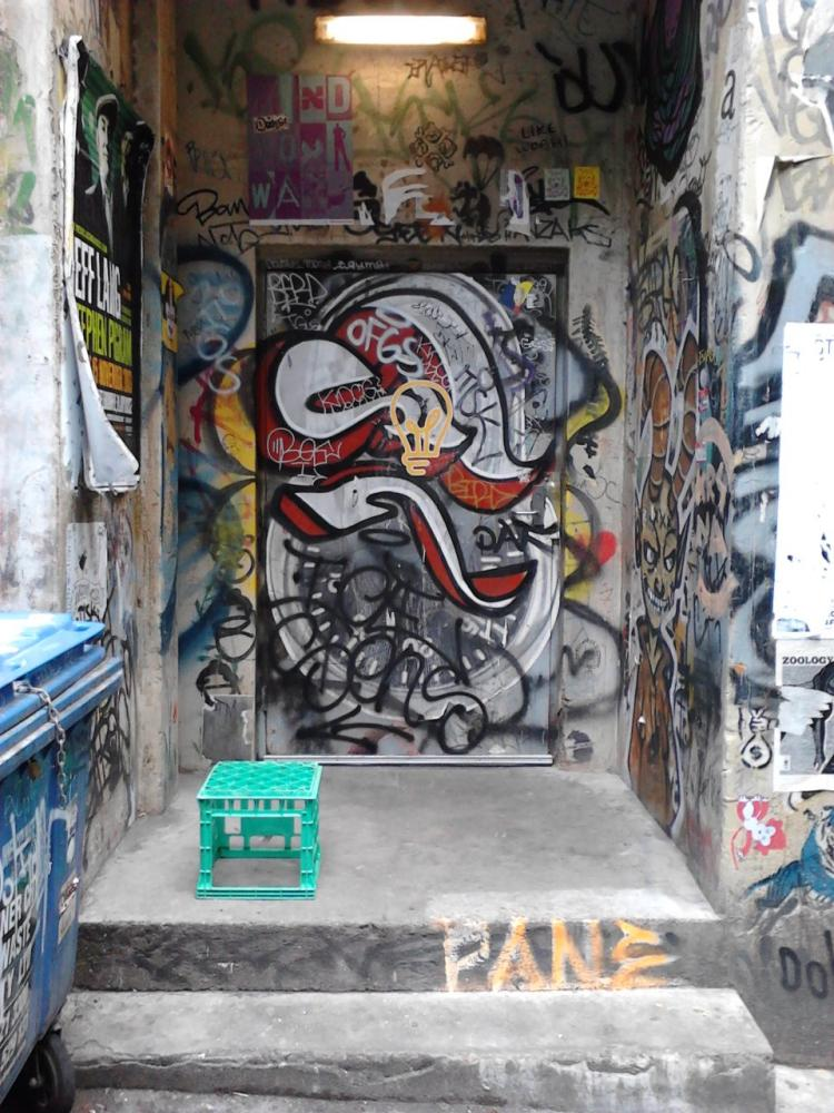 Doorway on ACDC Lane with three Banksy stencils
