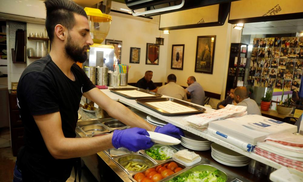 A worker prepares food for customers at a restaurant as Palestinians ease Covid-19 restrictions in Jenin.