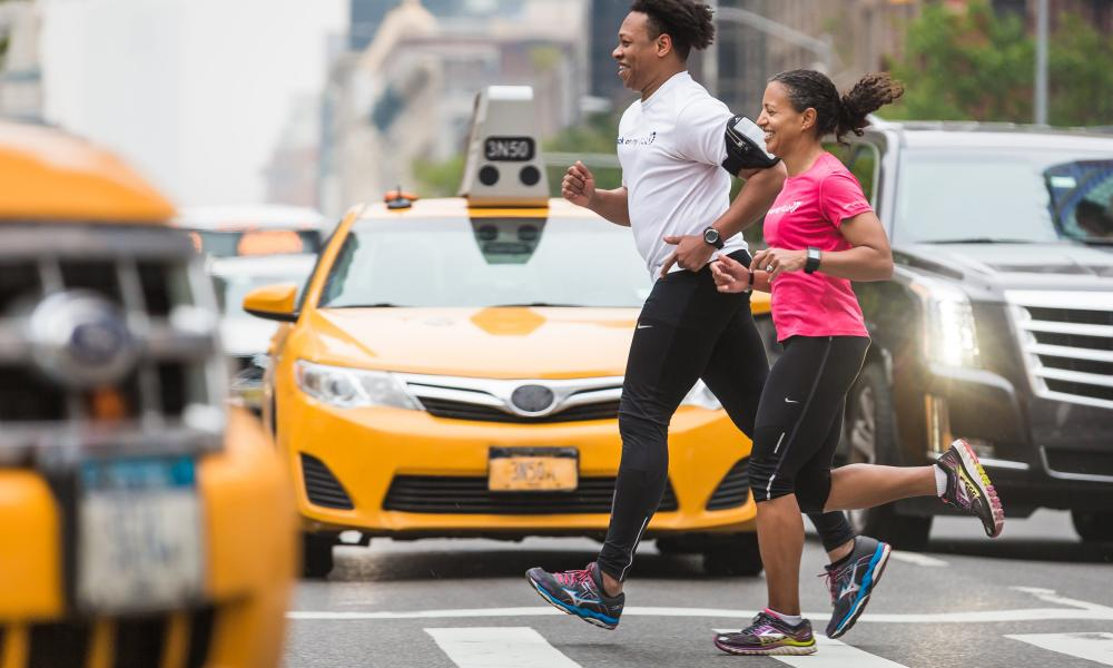 A woman and man jogging and/or running in a busy city.