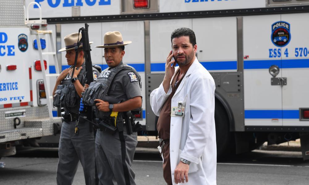 A hospital staff member talks on his phone as he walks past police outside the Bronx Lebanon hospital center.