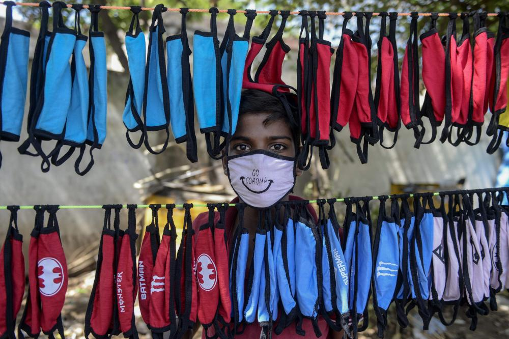 A street vendor poses as he arranges face masks to sell on the outskirts of Hyderabad.