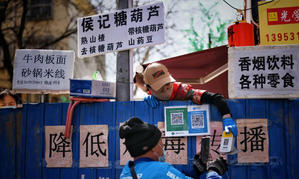 A deliveryman scans a QR code from an employee of a restaurant as he picks up food over barriers which has been set up to block an entrance to a food street in Jinan, Shandong province, China March 15, 2020.