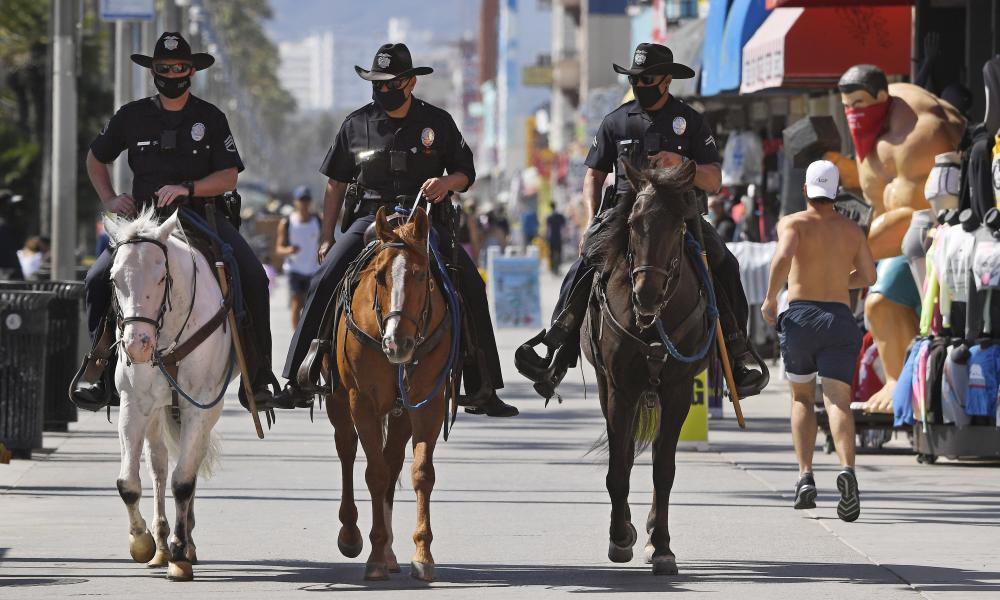 Los Angeles police officers patrol the Venice Beach boardwalk on horseback during the coronavirus outbreak, Wednesday, 13 May 2020, in Los Angeles.