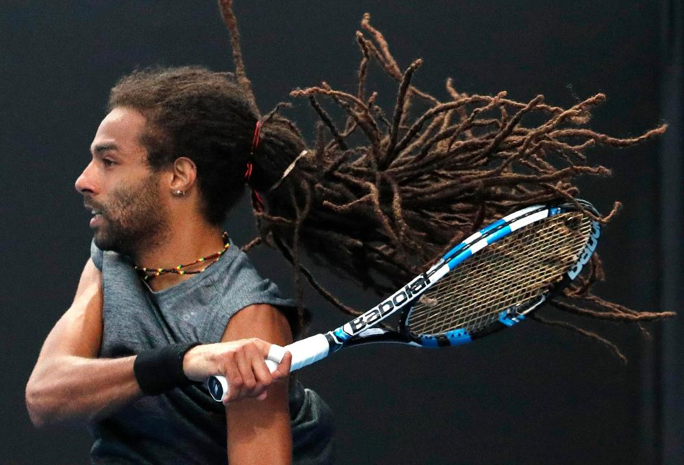 Dustin Brown bangs a forehand back to Pedro Sousa.