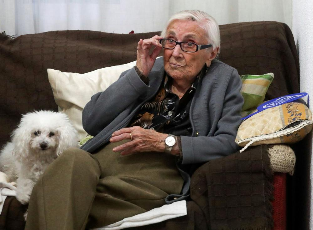 Florentina Martin, who survived coronavirus, sits on a sofa with her pet Luna as she watches TV in her home in Pinto, near Madrid.
