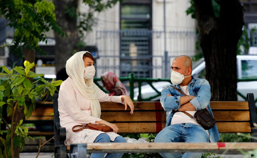 A man and a woman hang out on a bench in Tehran.