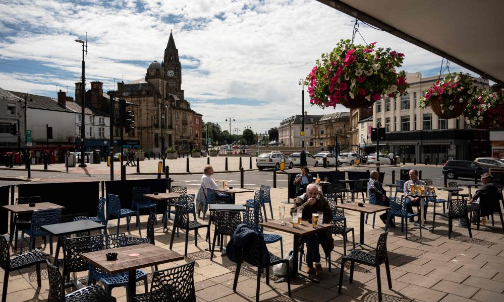 Drinkers sit outside a pub in Rochdale in Rochdale, greater Manchester, northwest England on July 30, 2020.